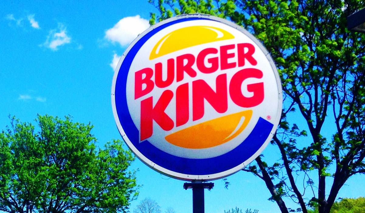 The Burger King sign hangs outside a restaurant.