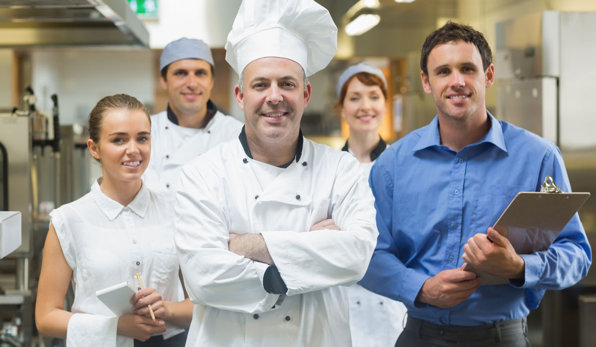 A chef stands with his team. Hiring a great staff is key to unlocking your restaurant's potential.