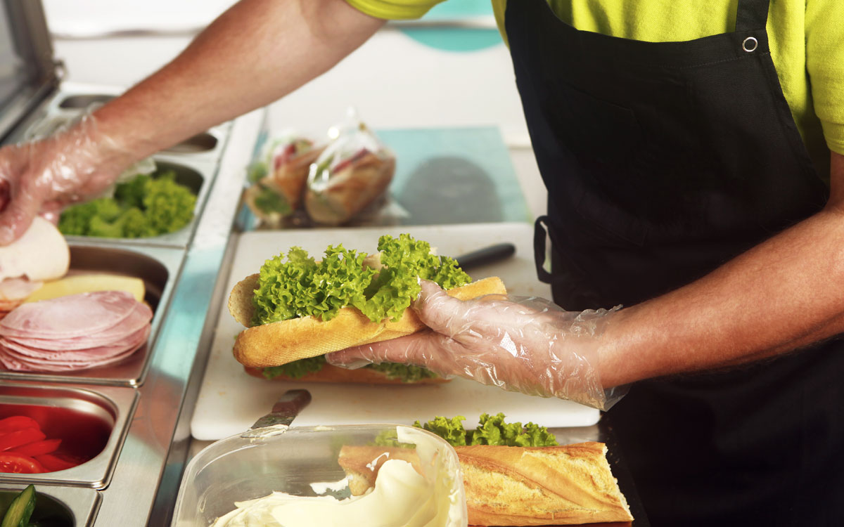 Fast-food worker makes a sandwich.