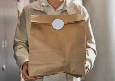 A restaurant employee carrying a brown paper bag of food.