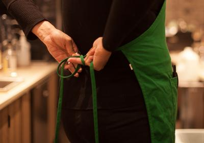 Starbucks employee ties their apron.