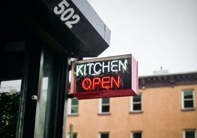 """Kitchen Open"" sign hangs outside a restaurant."