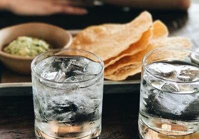 Two glasses of water on a table, with food in the background.