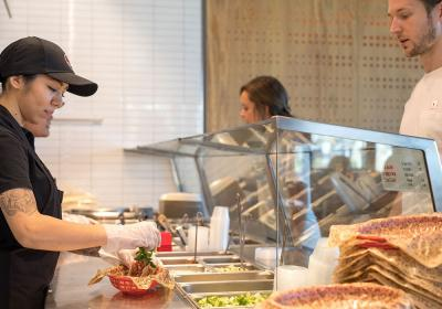 A Chipotle employee helps a customer.