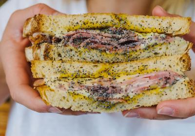 French Ham + Cheese comprised of hand carved French country ham, white American cheese, black poppy seeds and honey mustard vinaigrette on crispy sourdough.