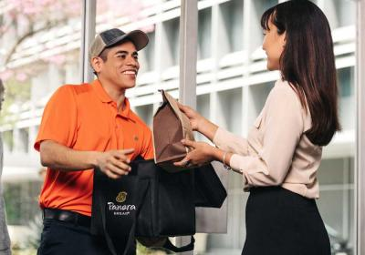 Panera Bread employee delivers food to a customer.