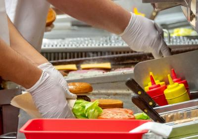 A fast-food worker prepares a burger in the back of the restaurant.