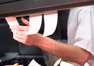 A restaurant worker looks at tickets in the kitchen.