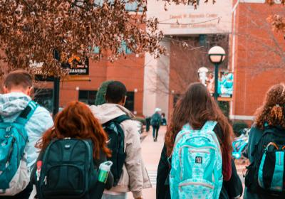 College students walk to class with their backpacks on.