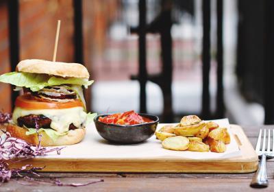 Hamburger, fries, and ketchup on a wooden plate.