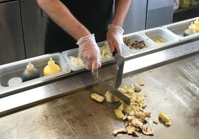 A worker cooks a sandwich on the flat top at Penn Station fast casual.
