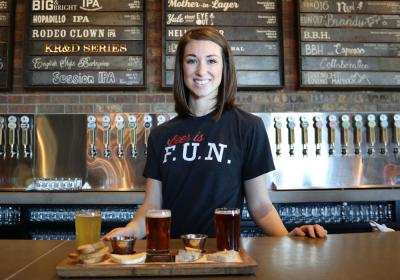 A bartender stands behind a flight of beers.