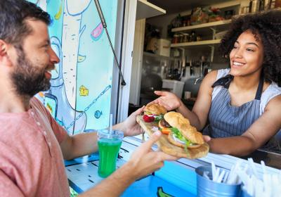 A woman hands a customer food through the window of a food truck.