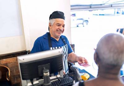 A senior hands a customer a card at a cash register.
