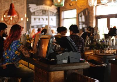 Customers sit around the bar of a crowded restaurant.