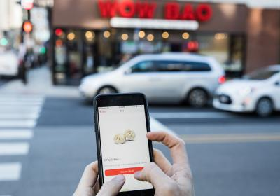 A Wow Bao customer holds up their phone to order food.