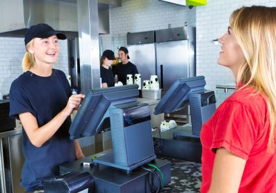 A fast-food worker takes a customer's order at the register.