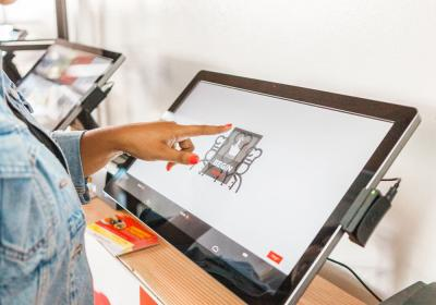 A Kitchen United customer uses a touch screen to order food.