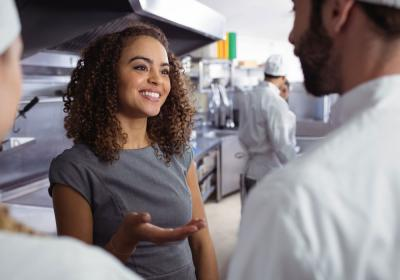 A young woman directs her team of chefs in the restaurant.