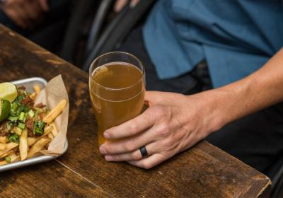 A man drinks a beer while eating fries on a wooden table.