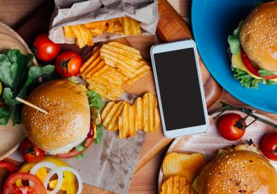 A mobile phone surrounded by plates of burgers and fries.