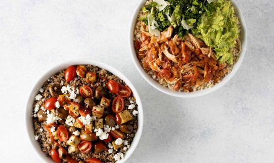 Two warm bowls on a plain background from Just Salad.