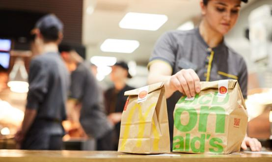 A McDonald's employee puts two bags of food on a counter.