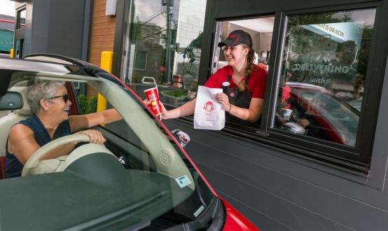 Wendy's employee serves a customer through the drive-thru lane.