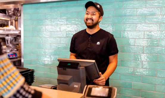 A Taco Bell employee takes an order at the register.