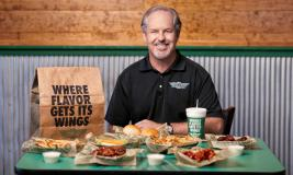 Charlie Morrison Wingstop CEO sits at a table.