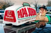 Papa John's deliver driver near a car.