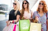 Three women shop for gift cards with bags.