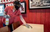 KFC employee cleaning tables.