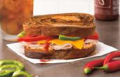 Bruegger's Bagels new winter menu includes bold sandwiches, like the Sweet Heat Turkey Sandwich, made with roasted turkey, cheddar cheese, crisp red and green bell peppers, and Sriracha sauce on butter-toasted marbled rye bread.
