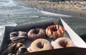 A box of Duck Donuts with the beach in the background.