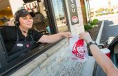 A Wendy's worker hands food out the window of a drive thru.