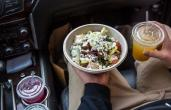 A Cava restaurant customer holds a bowl of food and a drink in the car.