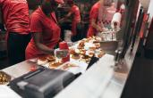 Five Guys workers prepare food in the back of the restaurant.