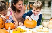 A parent carves pumpkin with her kids.