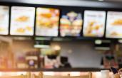 The blurry inside of a fast-food restaurant.