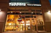 The front of a Toppers Pizza restaurant at night.