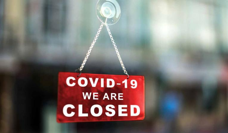 COVID-19 we are closed sign hangs in window.