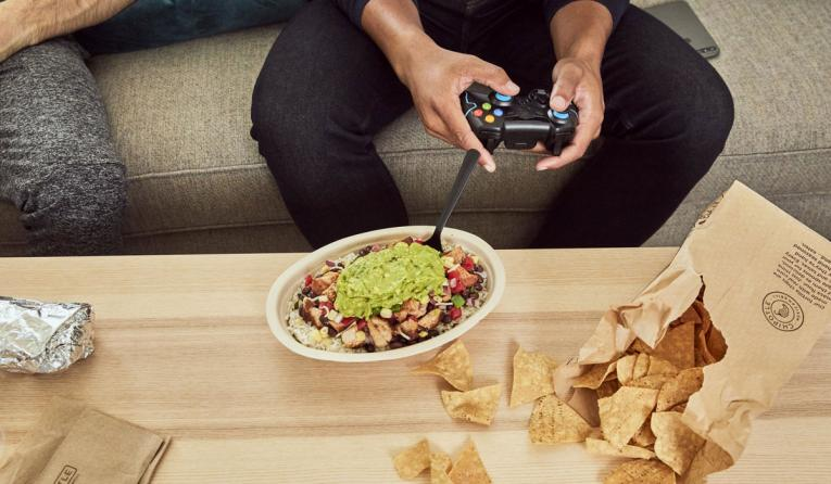 Someone plays video games with Chipotle on the table.