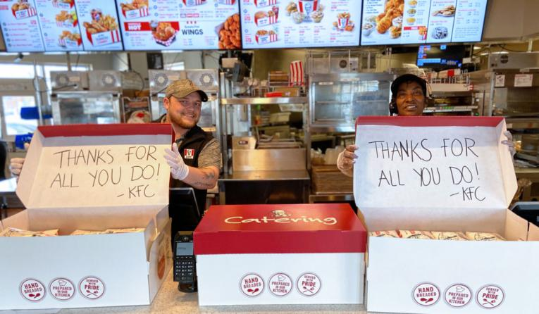 KFC employees stand behind boxes of chicken being given away.