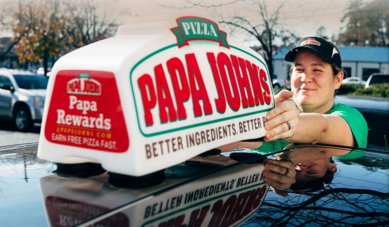 Papa John's deliver driver near a car.
