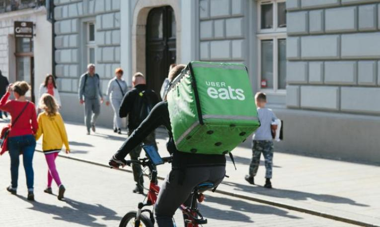 Uber Eats driver brings food on delivery.