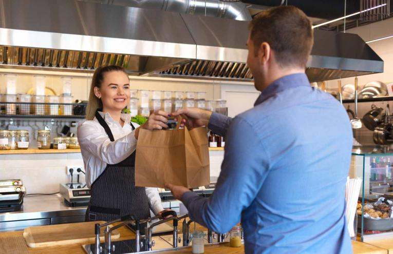A restaurant worker hands a bag of food to a guest.