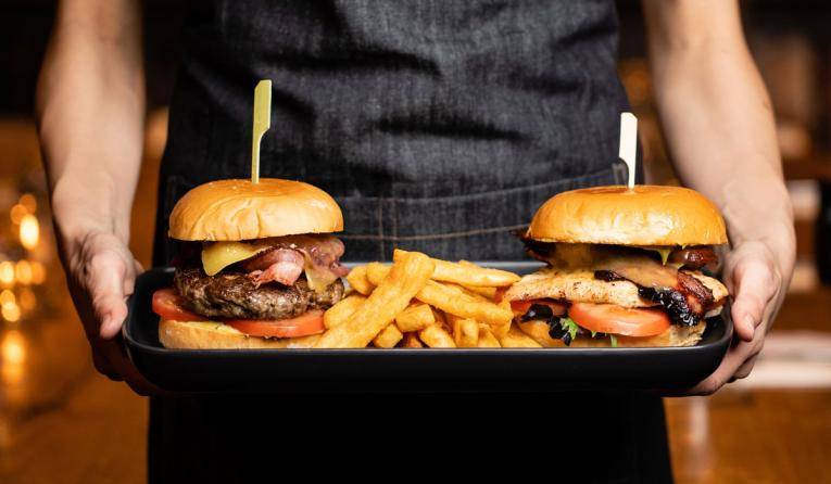 Two burgers being brought over by a waiter.
