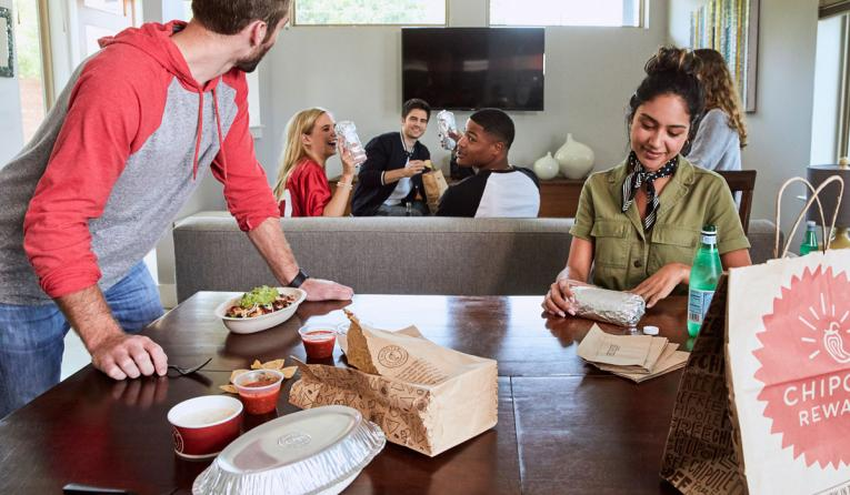 Customers gather around to eat Chipotle.