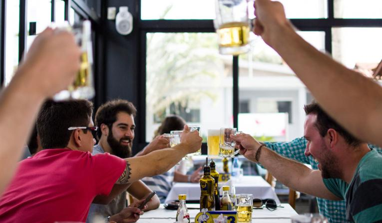 Restaurant customers cheers at a table with beers.